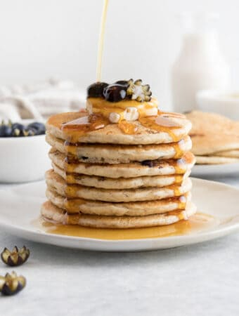 maple syrup poured onto blueberry pancakes