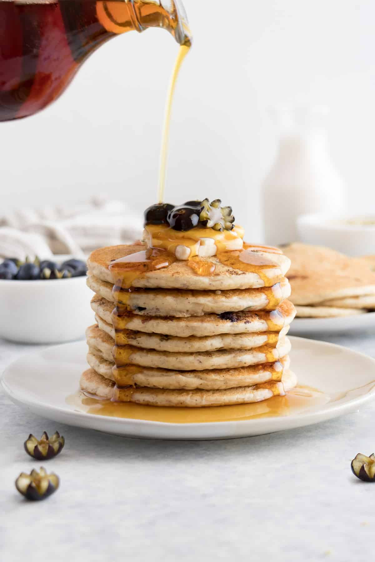 pouring maple syrup over a stack of vegan blueberry pancakes