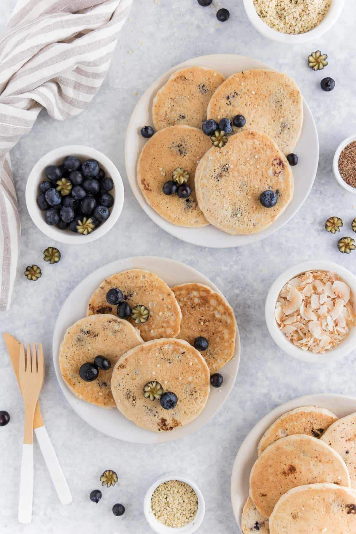 pancakes laying on two plates surrounded by blueberries, hemp seeds, and coconut flakes